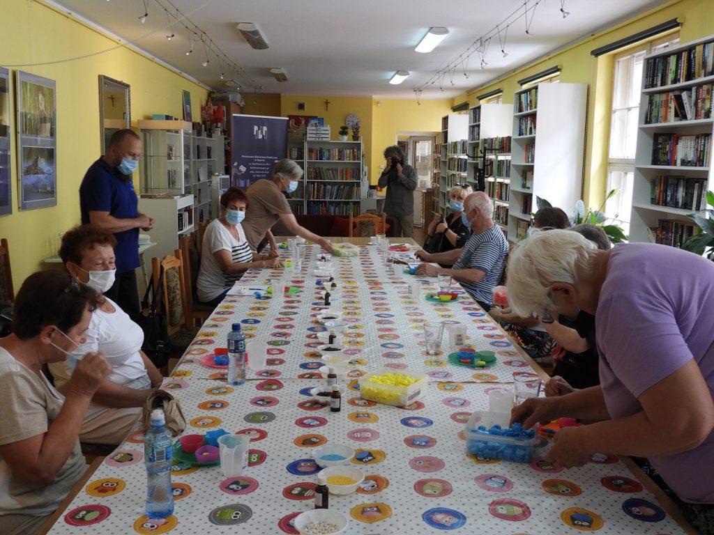 Na zdjęciu grupa 12 seniorów orazprowadzący podczas warsztatów ztworzenia mydeł. Osoby pracują przy stołach. Wtle dyrektor biblioteki Wiesław Walas zaparatem fotograficznym.