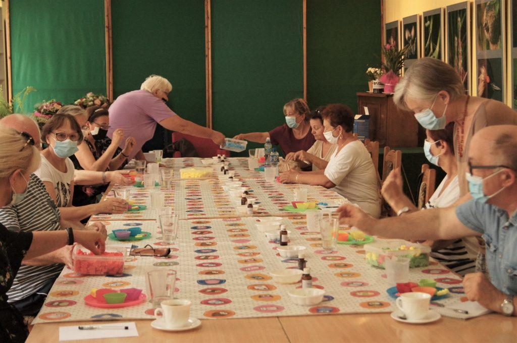 Na zdjęciu grupa 12 seniorów orazprowadzący podczas warsztatów ztworzenia mydeł. Osoby pracują przy stołach.