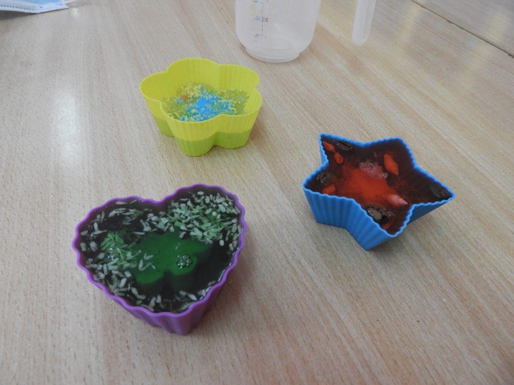 Na zdjęciu są trzy kolorowe mydełka wforemkach silikonowych.