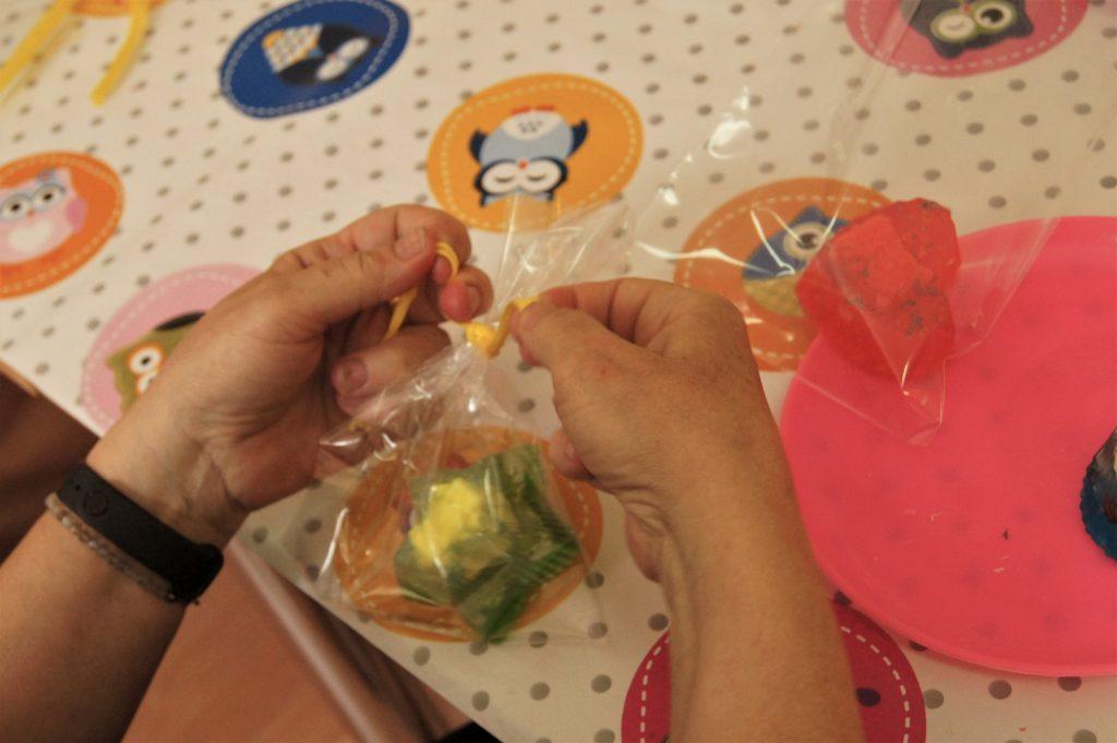 Na zdjęciu dłonie uczestnika warsztatów, które pakują mydełko wcelofanowy woreczek.