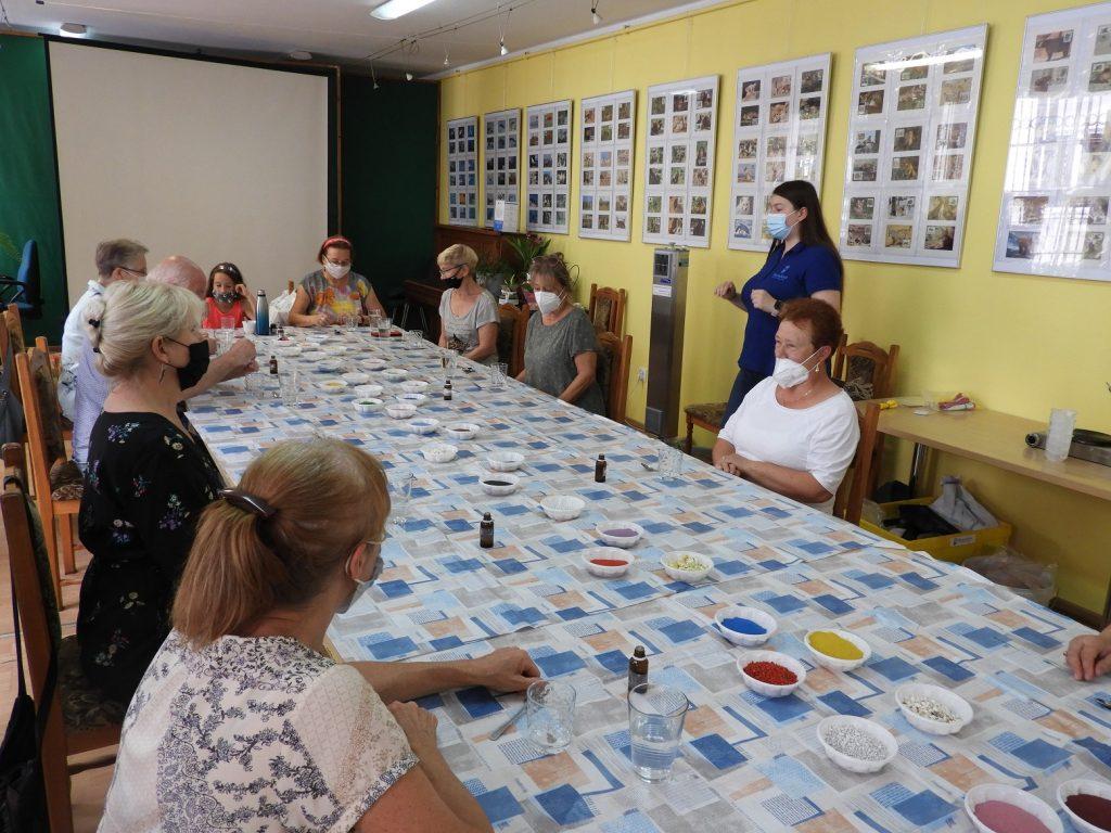 Na zdjęciu grupa seniorów orazprowadząca podczas warsztatów ztworzenia świeczek. Osoby pracują przy stołach.