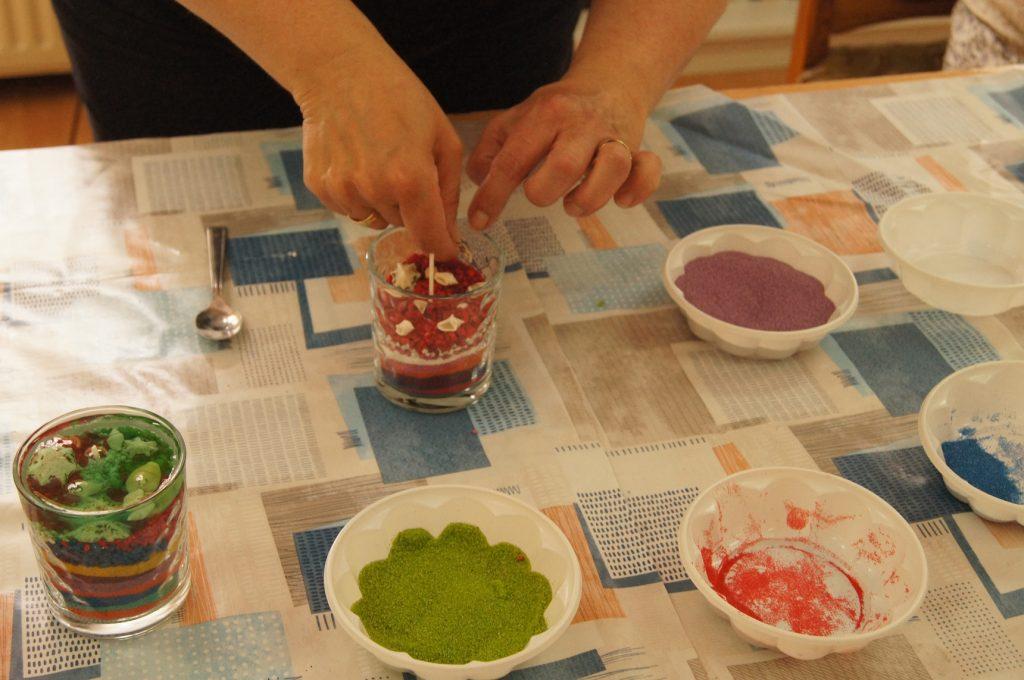 Na zdjęciu widać proces układania kolorowych pasków warstwami wszklanym naczyniu.