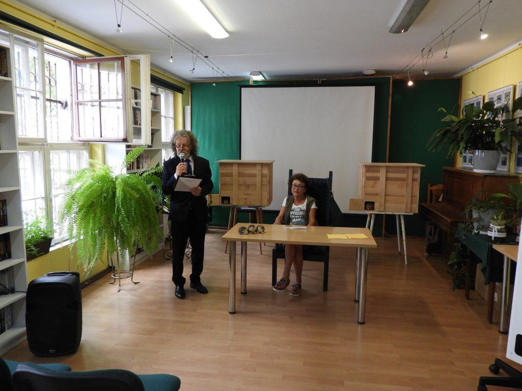 Na zdjęciu pani Dorota Sumińska siedzi zastolikiem. Obok niej stoi dyrektor biblioteki Wiesław Walas, którywręku trzyma mikrofon. Zanimi wtle widać dwa całoroczne domki dla jeży.