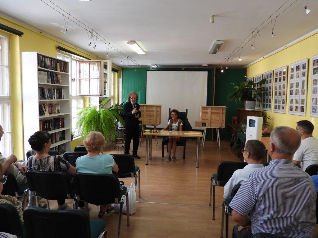 Na zdjęciu pani Dorota Sumińska siedzi zastolikiem. Obok niej stoi dyrektor biblioteki Wiesław Walas, którywręku trzyma mikrofon. Zanimi wtle widać dwa całoroczne domki dla jeży. Twarzami dopani Doroty siedzą ludzie, którzyprzyszli naspotkanie.