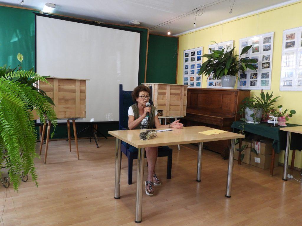 Na zdjęciu pani Dorota Sumińska siedzi zastolikiem. Wręku trzyma mikrofon. Zanią wtle widać dwa całoroczne domki dla jeży.