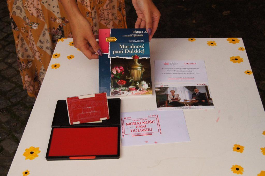 Zdjęcie przedstawia książkę Moralność pani Dulskiej orazokolicznościową pieczęć Narodowego Czytania ikartkę odpary prezydenckiej.