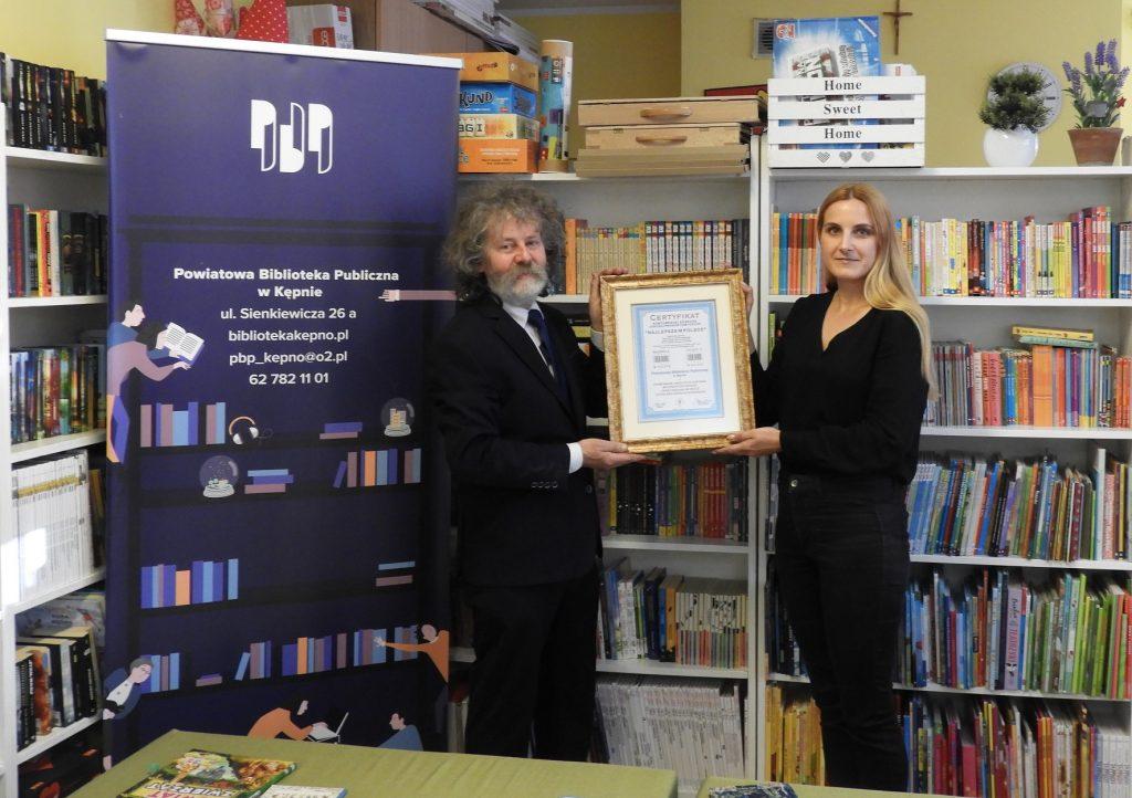 """DyrekAtor biblioteki orazbibliotekarz trzymają certyfikat """"Najlepsze wPolsce"""" przyznany Powiatowej Bibliotece Publicznej wKępnie. Stoją natle regałów zksiążkami. Obok dyrektora stoi rollup biblioteki."""