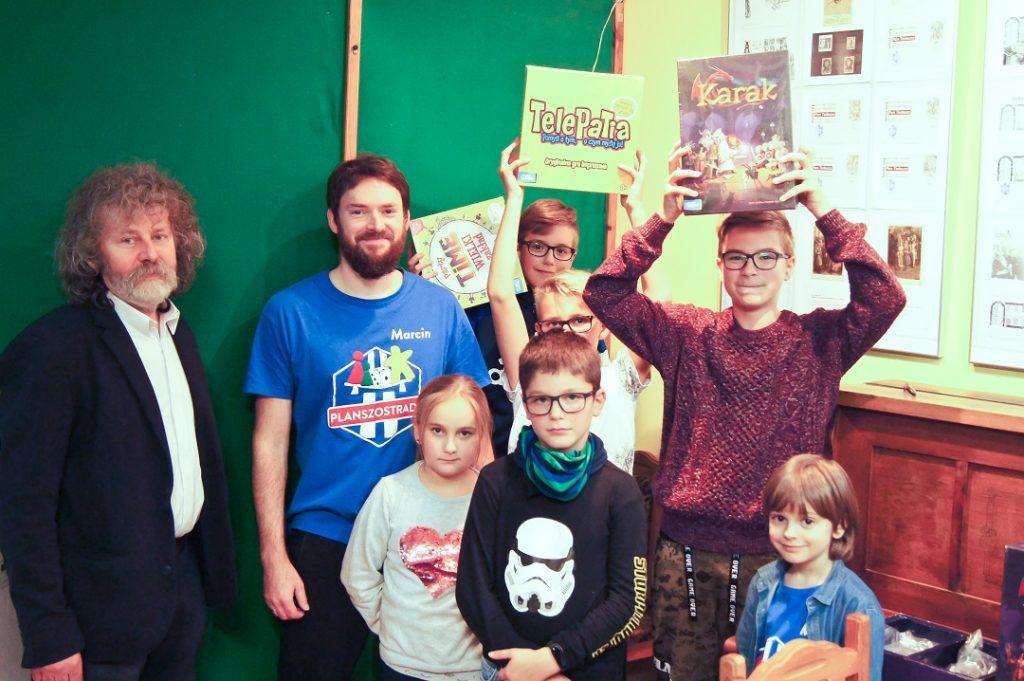 Na zdjęciu natle zielonej ściany ifortepianu pozują dyrektor biblioteki powiatowe, Marcin szalek zPlanszostrady orazmali laureaci konkursu nagrę planszową. Trzymają oni wrękach wygrane gry.